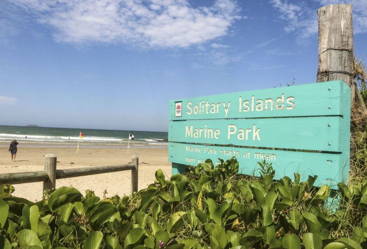 Solitary Islands Marine Park sign at beach with surf safety flags