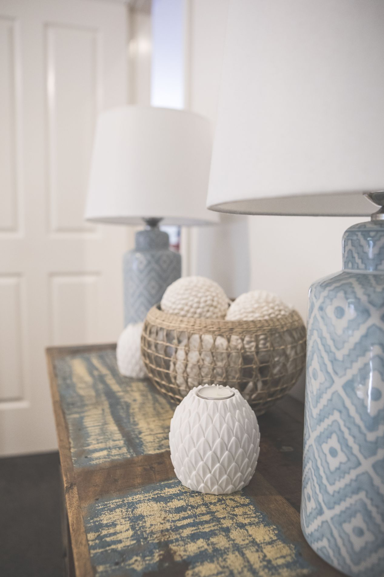 Blue patterned ceramic lamps with basket of decorative homewares on distressed wood console