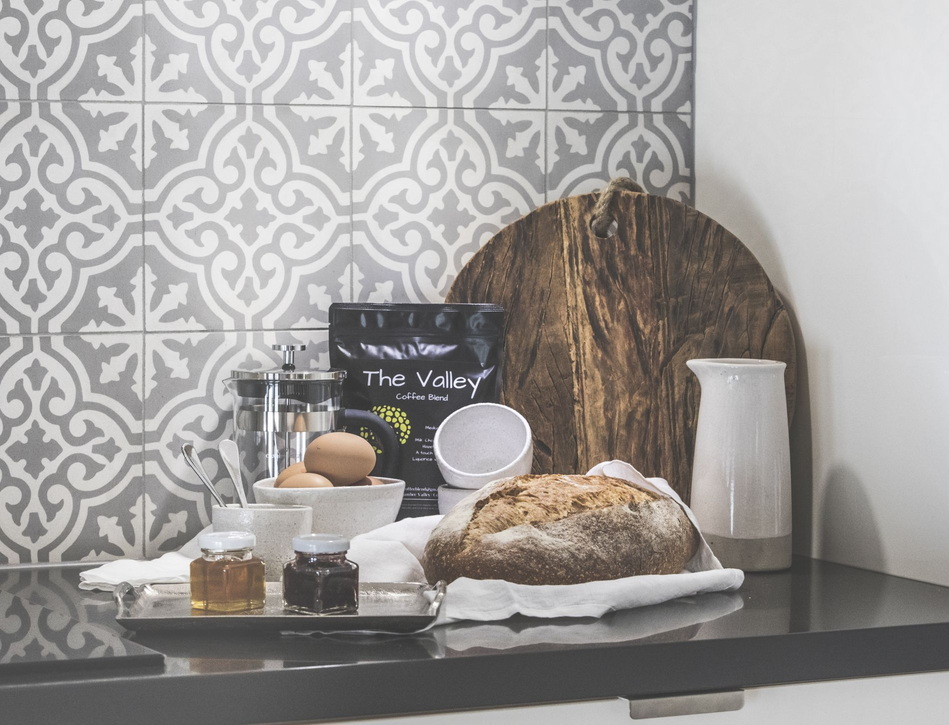 An assortment of sourdough jam fresh eggs and the valley coffee against a grey patterned tile and bread board at diggers beach cottage