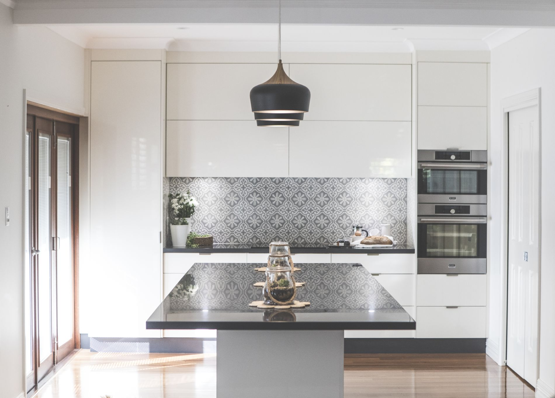 Kitchen corian island with centerpieces and patterned backsplash stylish contemporary lighting at Diggers Beach Cottage