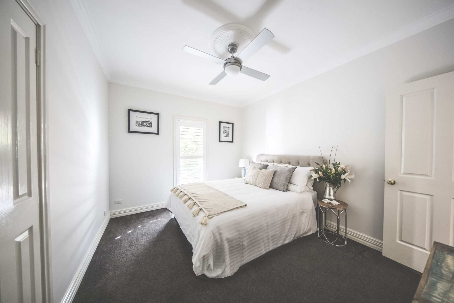 Soft linens and cushions in second bedroom with carpet and ceiling fan and fresh flowers bedside